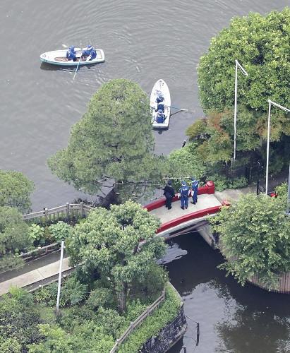碑文谷公園内の池を調べる警視庁の捜査員ら(23日午後2時36分、東京都目黒区で、読売ヘリから)